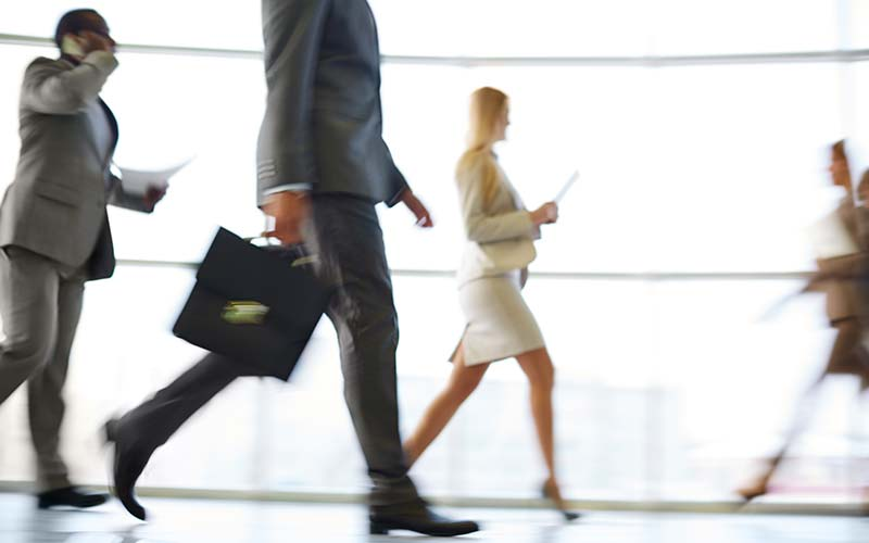 business people hurry through building lobby
