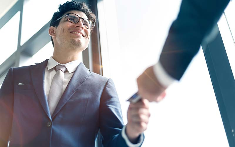 two businessmen exchange a business card