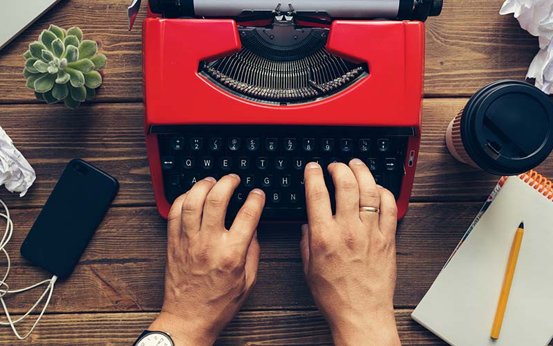 image of a man's hands typing on a red vintage typewriter